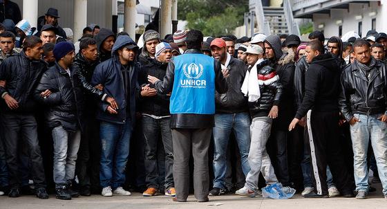 Un trabajador de el Alto Comisionado de las Naciones Unidas habla con un grupo de inmigrantes llegados desde Túnez a la isla Lampedusa, Italia.