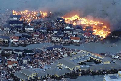 Viviendas en llamas y rodeadas de toneladas de escombros junto al río Natori, desbordado por las olas del tsunami, en la ciudad homónima.