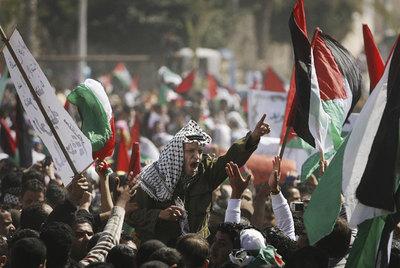 Manifestantes ondean banderas palestinas en Gaza para pedir el fin de la división entre Fatah y Hamás.