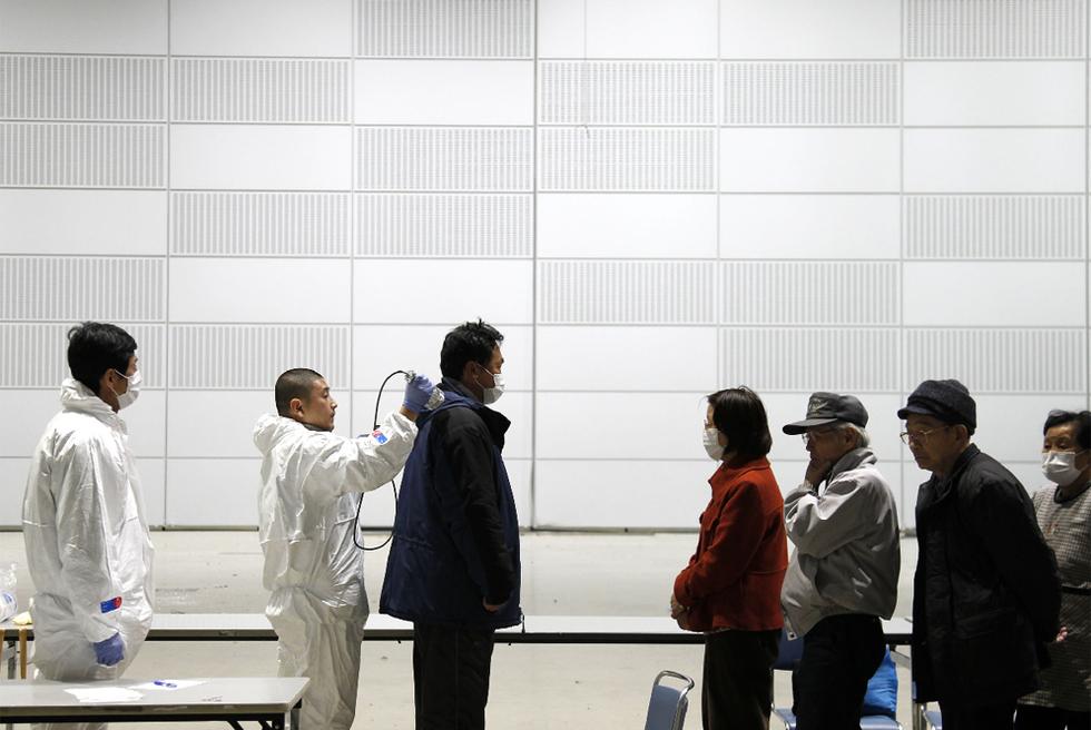 Un grupo de personas se somete a un examen de detección de radiactividad en Koriyama, a 80 kilómetros de Fukushima.