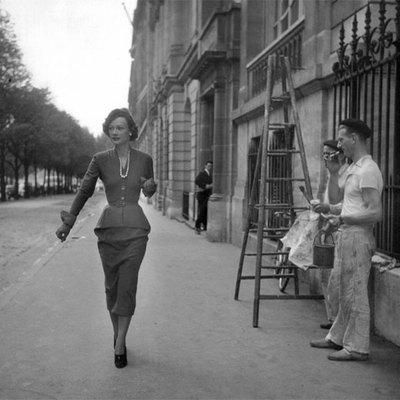 Unos obreros observan a una mujer vestida de última moda hace décadas.