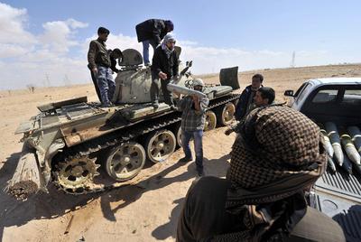 Milicianos rebeldes descargan proyectiles de un tanque de las tropas de Gadafi.