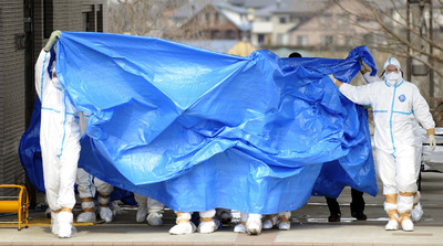 Varios operarios que trabajan en la reparación de la central de Fukushima I salen de la misma bajo una lona.