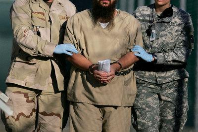 Dos soldados conducen a un preso esposado en el penal de Guantánamo en 2006.