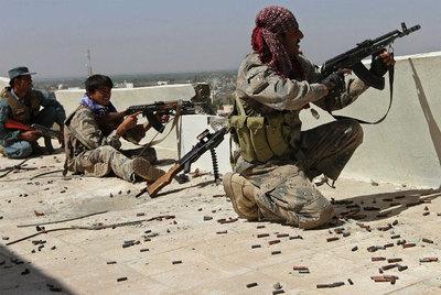 Policías afganos disparan a las fuerzas talibanes desde el tejado de un edificio en Kandahar.