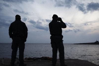Dos agentes de la Guardia de Finanzas italiana controlan el tránsito de barcos desde Lampedusa.