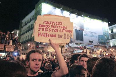 Un joven exhibe un cartel contra la clase política en la concentración de anoche en la Puerta del Sol.