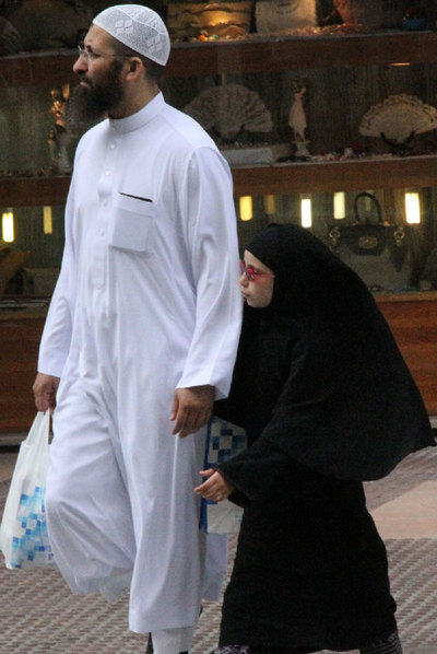 Un padre camina con su hija  por la avenida Juan Carlos I, en el centro de Melilla.