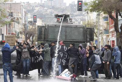 Un vehículo policial dispara agua a presión a un grupo de manifestantes en Santiago.