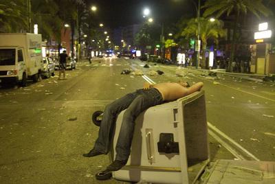 Un joven duerme sobre un contenedor de basura volcado en la calle principal de Lloret de Mar.