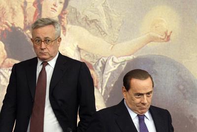 El primer ministro italiano, Silvio Berlusconi, sentado, junto al titular de Economía, Giulio Tremonti, el pasado viernes.