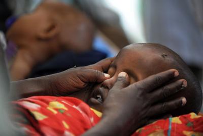 Una madre cierra los ojos a su hijo, que acaba de morir, en Mogadiscio.