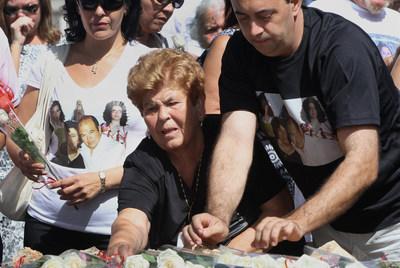 Familiares depositan flores en las placas que recuerdan en Barajas a los fallecidos.