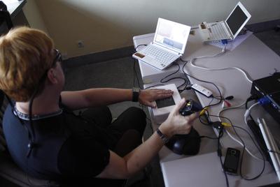 Usuario probando las gafas conectadas a un ordenador .Con una mano detecta lo que se muestra en relieve sobre una placa y con otra maneja el dispositivo con un control.