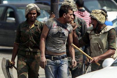 Dos soldados egipcios detienen a un hombre que intentaba acercarse a la Embajada israelí, ayer en El Cairo.