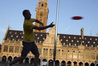 Un hombre juega al  frisbee  ante la Biblioteca de la Universidad de Lovaina