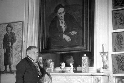 La escritora Gertrude Stein, en su casa de París, ante su célebre retrato  pintado por Picasso.