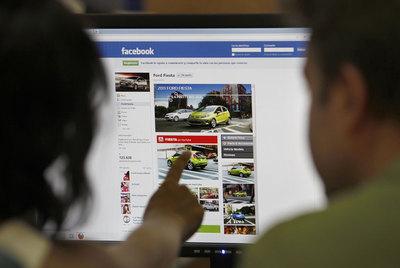 Una pareja busca información sobre automóviles en Facebook.