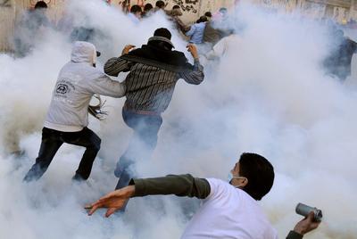 Un manifestante se dispone a devolver un bote de humo a las fuerzas de seguridad mientras otros huyen de la nube de gases lacrimógenos en la plaza de Tahrir.