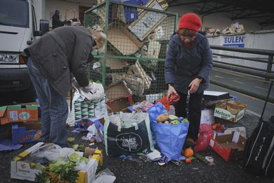 Dos personas recogen comida de la basura en Madrid, en diciembre.