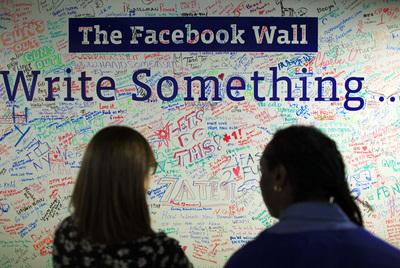 Dos mujeres leen un muro con mensajes instalado en la oficina de Facebook en Nueva York.