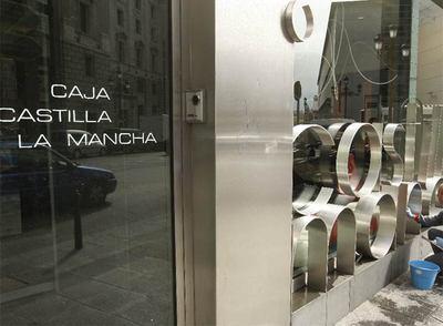 Un empleado limpia la fachada de la sede de Caja Castilla La Mancha en Madrid.
