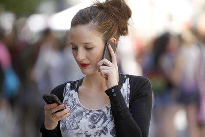 Una joven se comunica por dos teléfonos móviles al mismo tiempo en una calle de Madrid.