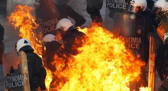 Policías griegos atacados con cócteles molotov durante las protestas del domingo en Atenas.