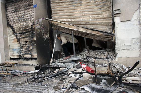 Un empleado sale de un banco incendiado el domingo.