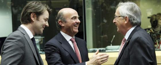 El ministro de Economía, Luis de Guindos, con el presidente del Eurogrupo, J. C. Juncker, y el ministro de Finanzas galo, F. Baroin.