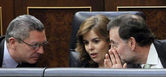 El presidente del Gobierno, Mariano Rajoy, hace confidencias a la vicepresidenta, Soraya Sáenz de Santamaría, y al ministro de Justicia, Alberto Ruiz Gallardón.