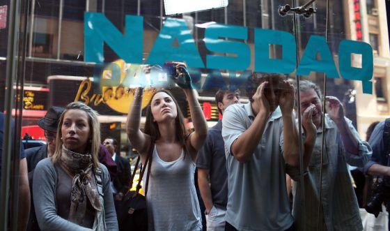 Un grupo de curiosos miran a través de los cristales del Nasdaq en el día del estreno.