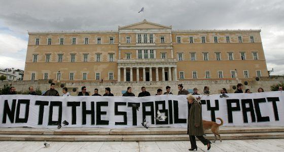 """Activistas sostienen una gran pancarta en la que se lee """"no al pacto de estabilidad"""" delante del Parlamento griego en Atenas."""