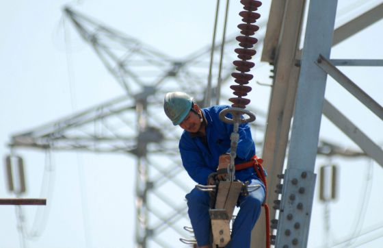 Un trabajador instala nuevas líneas de alto voltaje en una torre de electricidad.