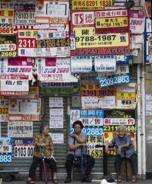 Tres mujeres sientan delante de una tienda cubierta por anuncios de venta y alquiler en Hong Kong.