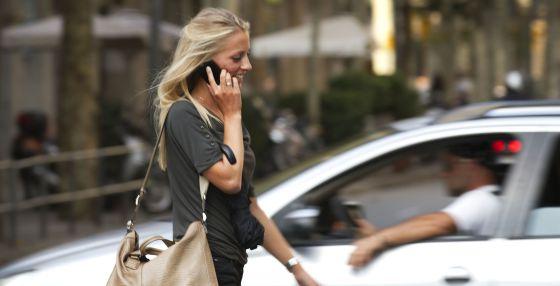 Una mujer joven camina hablando por su teléfono móvil por Barcelona