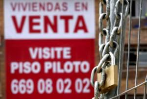 En la imagen, un cartel anunciador de venta pisos cuelga de una fachada de una nueva promoción en Madrid.