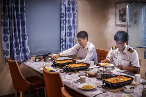 El capitán (izquierda) y el primer oficial, Bae Jeong-Hoo, cenando. / ALFREDO CÁLIZ