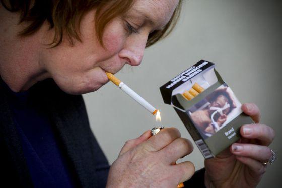 Una mujer enciende un cigarrillo.