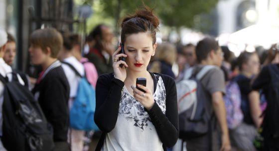 Una joven con dos teléfonos móviles en Madrid.
