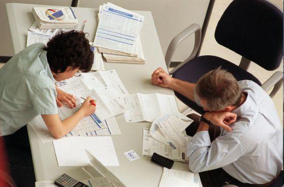 Dos personas rellenan los impresos en una delegación de Hacienda.