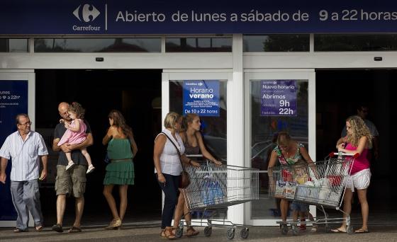 Varias personas en la zona de acceso de un hipermercado Carrefour de Málaga.