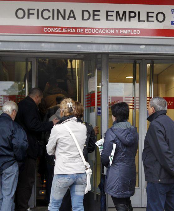 Ciudadanos hacen cola ante la oficina de empleo de un barrio de Madrid.