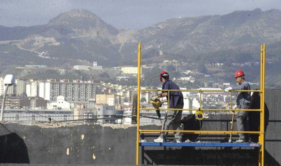 Unos obreros, en el andamio de una obra, en Ceuta.