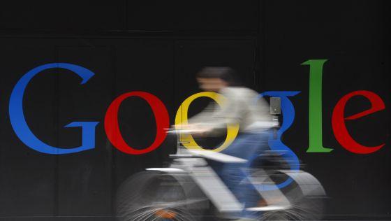 Un empleado de Goolge pasa montado en su bici ante su sede de Zurich.