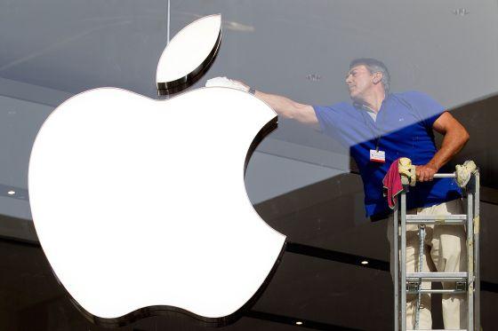 Un hombre limpia el logotipo de Apple en una tienda de Barcelona