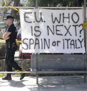 """Un policía ante una pancarta en la que se puede leer """"Unión Europea, ¿Quién es el siguiente? España o Italia"""" frente al Parlamento en Nicosia"""