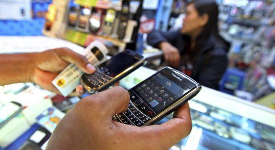 Un cliente sostiene dos teléfonos móviles BlackBerry