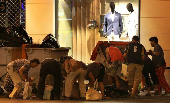 Un grupo de personas busca en bolsas de basuras alimentos a las puertas de un centro comercial de Madrid.