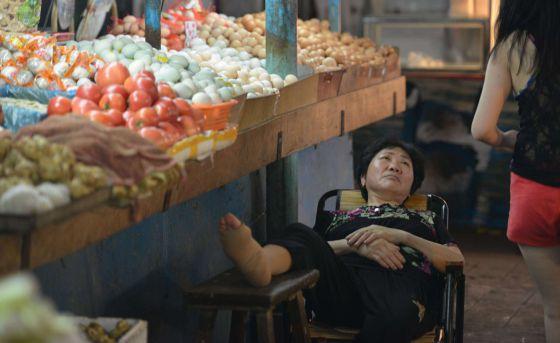 Una vendedora descansa en un mercado de Shanghai